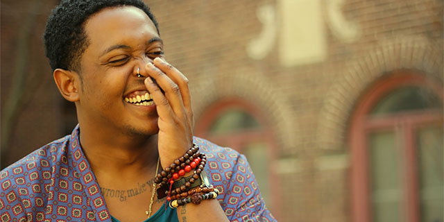 Danez Smith laughing with hand over their mouth