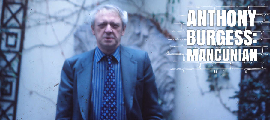 Anthony Burgess standing in front of a wall in Manchester