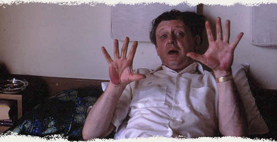 Burgess gesturing in a hotel room
