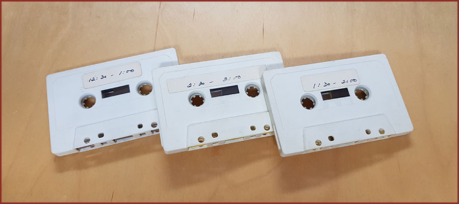 Three cassette tapes on sparse background